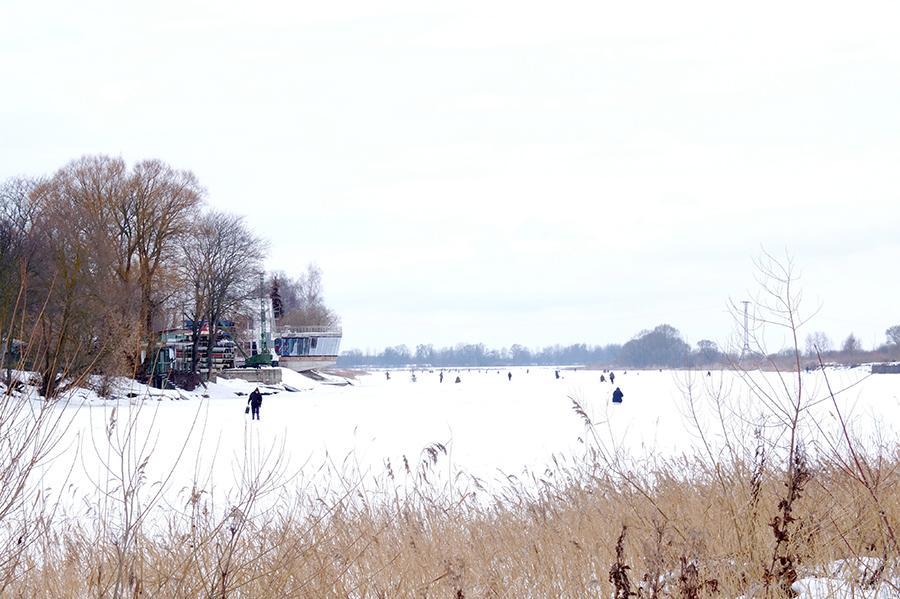 Zamrzlá řeka nedaleko Jelgavy, futuristická restaurace a pár rybářů na řece.