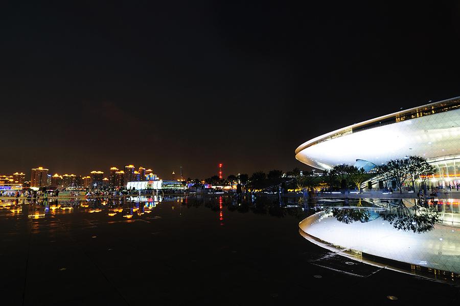 Kulturní centrum a v pozadí svítící šanghajské sídliště.