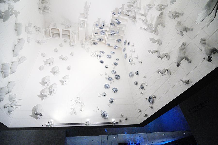 Porcelán jako by vypadával ze skříněk na stropě. Nebo spíše vystupoval?