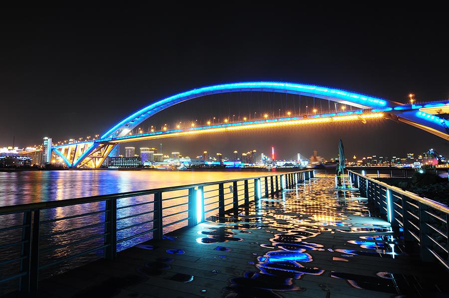 Lupu Bridge byl klasicky čínsky nasvícený - a opět proměnně, chvíli byl červený, tu zelený, modrý... Bylo zrovna namoklo, takže odrazy mostu byly parádní. A řeku pod ním brázdily obrovské nákladní lodě...