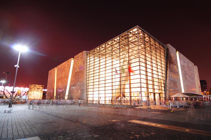 Prosklené pavilony krásně vystupovaly proti temné obloze. Toto je Italský pavilon s replikou vítězného oblouku uvnitř.