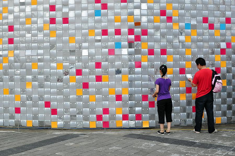 Fasáda lotyšského pavilonu složená z volně zavěšených barevných plastových štítků lákala k prohlédnutí.