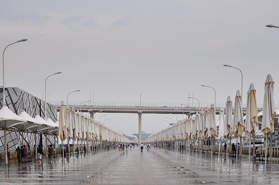 Vysoko nad vyvýšeným chodníkem se tyčí most přes řeku Jang-c-tiang (Dlouhá řeka).