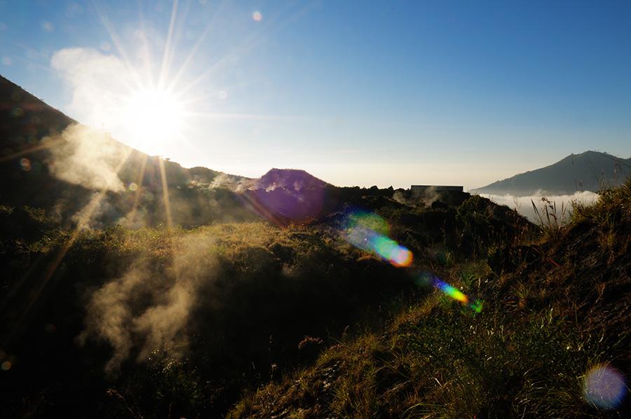 Slunko se vyhouplo nad hranu vulkánu, rozhánějíc mraky kdesi pod námi.