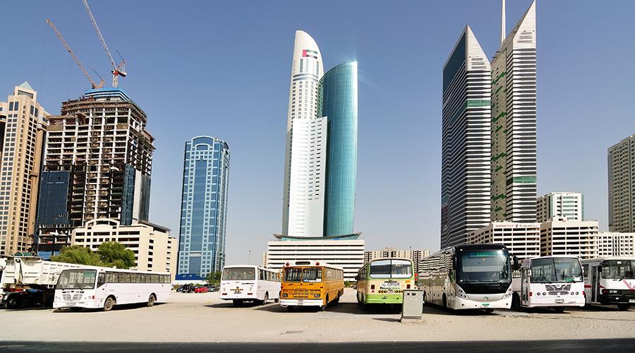 Parkoviště plná autobusů, dovážejících dělníky z periferie...